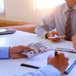 image of a man signing a mortgage or insurance contract or the deed of sale when buying a new house or selling his.